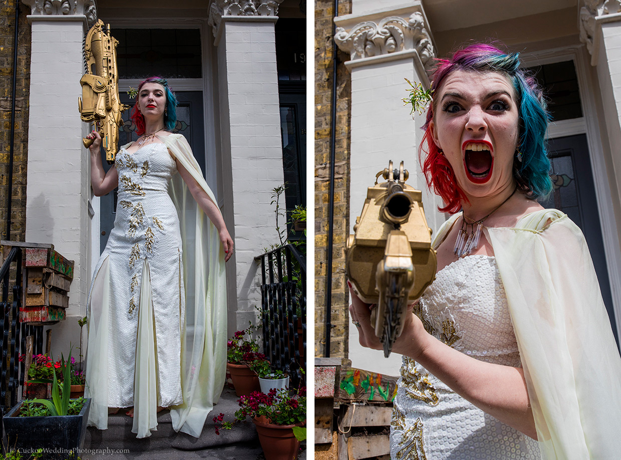 A quirky alternative bride in a white dress with red and blur dyed hair holds a large gold space gun and stands with attitude.