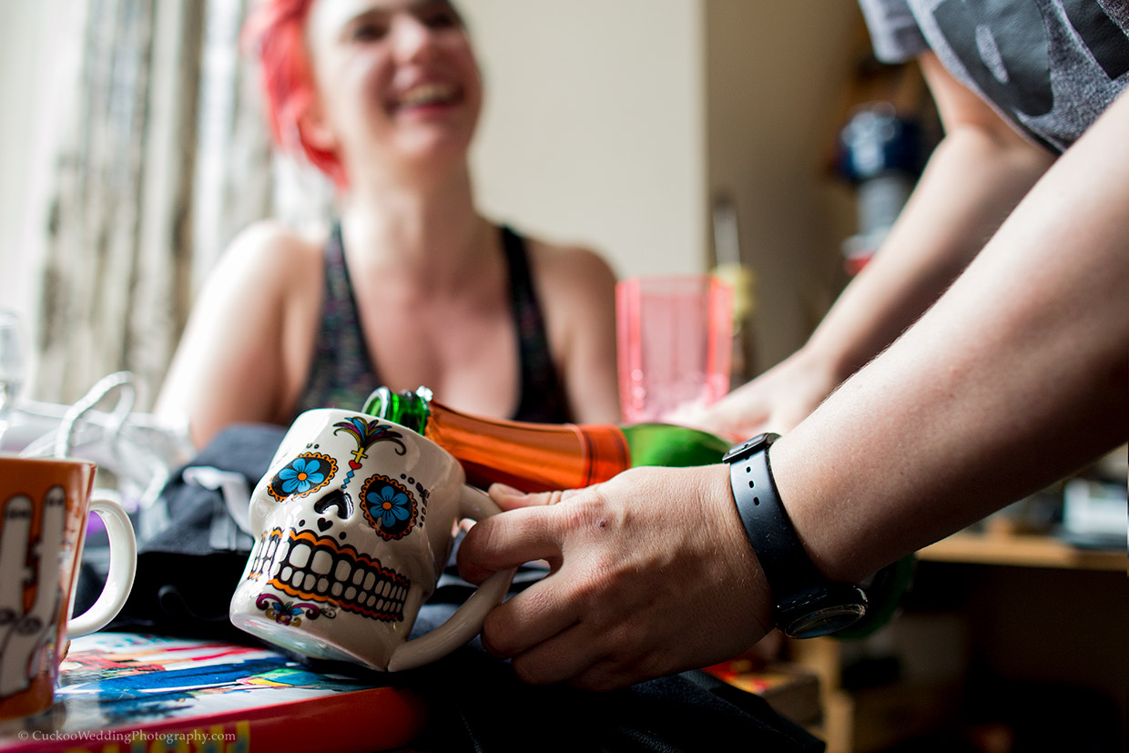 A Mexican skull cup is filled with champaign from a bottle. the bride is blurred in the background