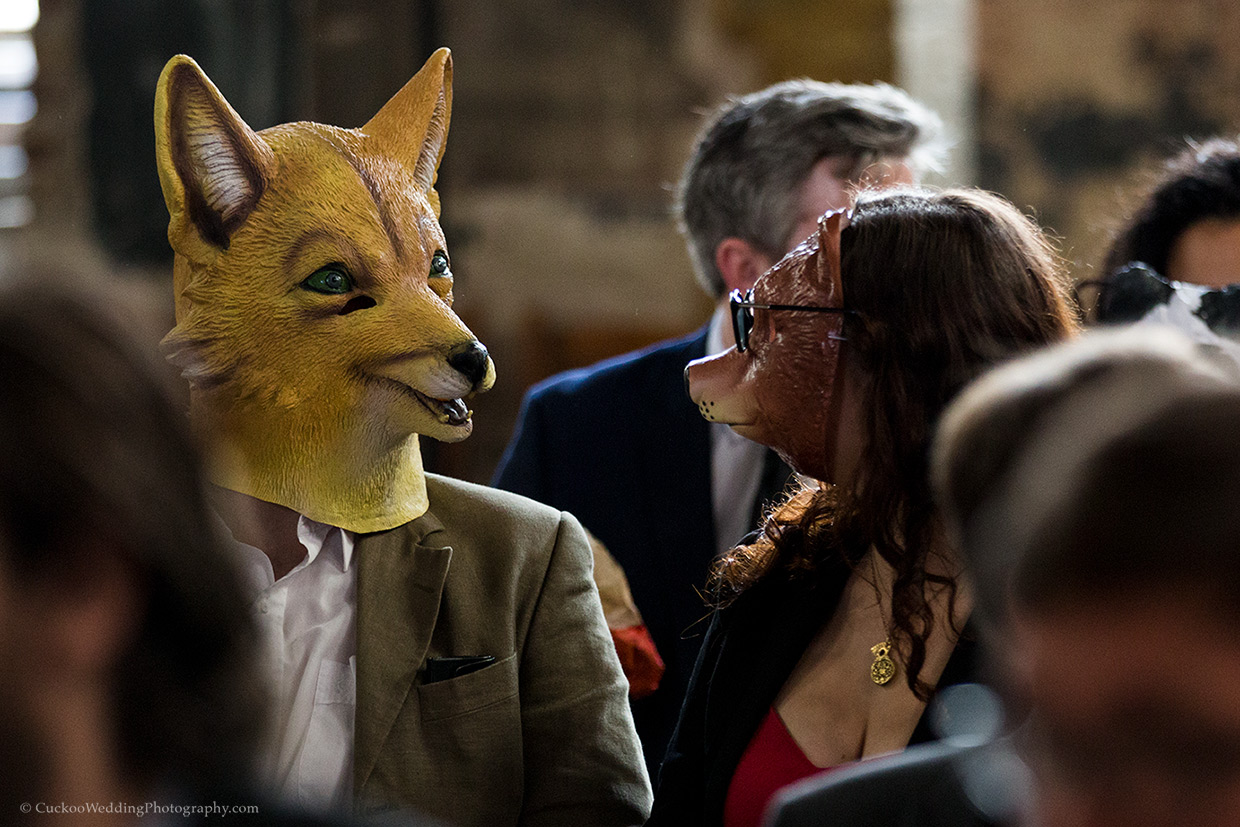 A man wearing a yellow wolf mask and a woman wearing a brown bear mask at a wedding in Asylum Chapel London.