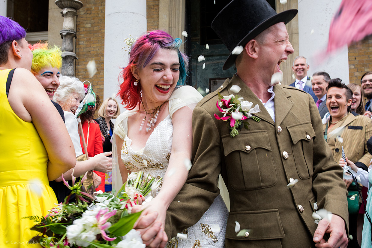 Wedding guest throw confetti as the wedding couple leave Asylum Chapel in London, they are holding hands, the bride has pink and blue hair.