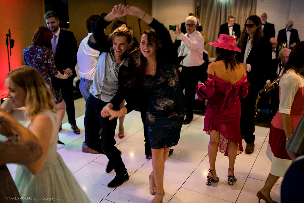 Guest dance dramatically on the dance floor at a wedding