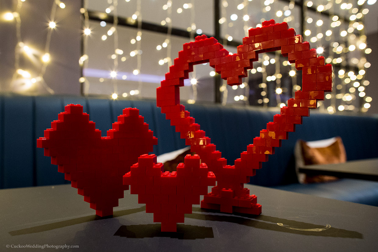 A heart made out of red Lego block on a table in a bar