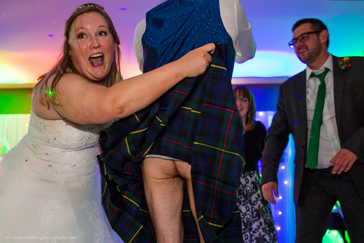 A bride is lifting the kilt of a Scottish groom to reveal that he is naked underneeth