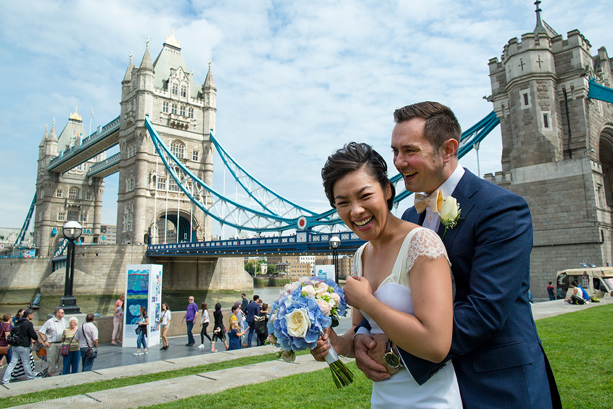 Unique bride and groom are smiling in font of Tower Bridge in London, it's a sunny day.