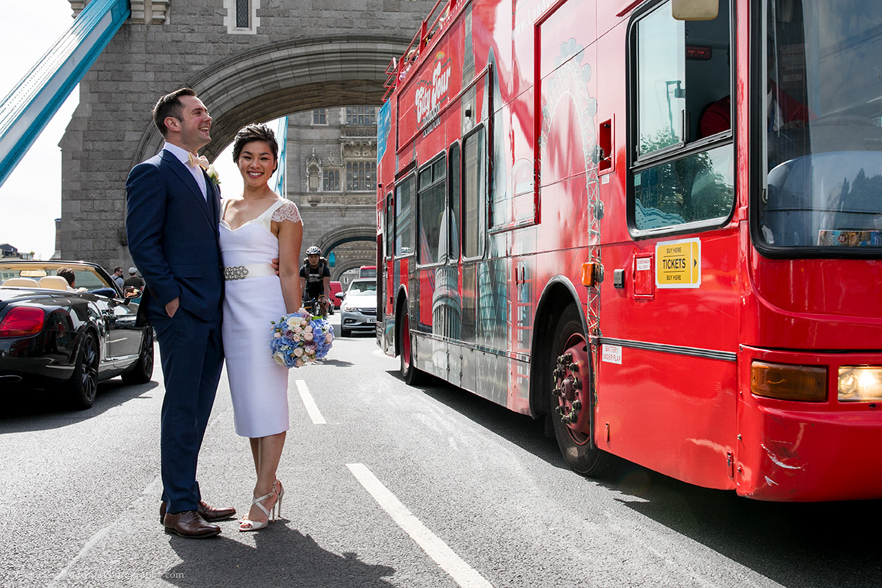 Unique bride and groom are smiling. Tower Bridge in London is in the background. It's a sunny day.