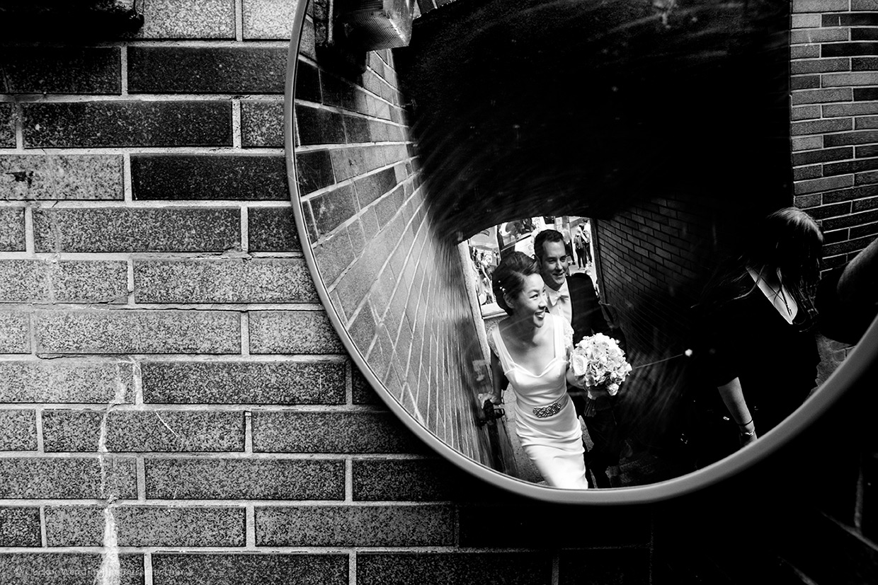 Unique bride and groom are smiling while walking up stairs reflected in a mirror