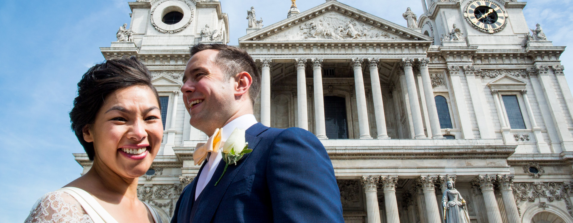 Unique bride and groom are smiling in font of St Paul's Cathedral, its a sunny day.