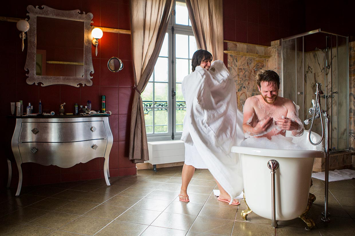 A wedding photograph of a relaxed fun bride and groom in a big bathroom, the groom is in the bath and the bride has a towel ready for him, the room is red.