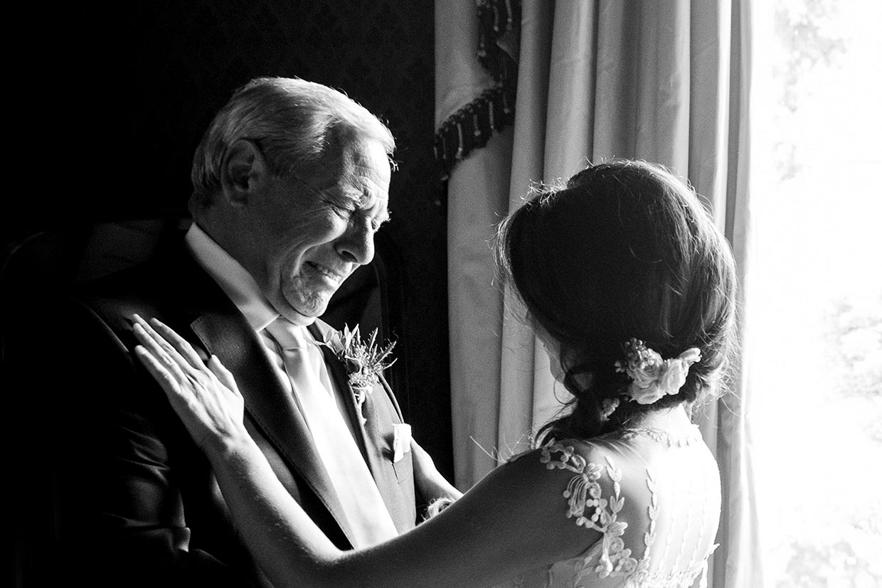 A wedding photograph of a father looking at his daughter who is a bride, the father is shoeing lots go happy emotion.