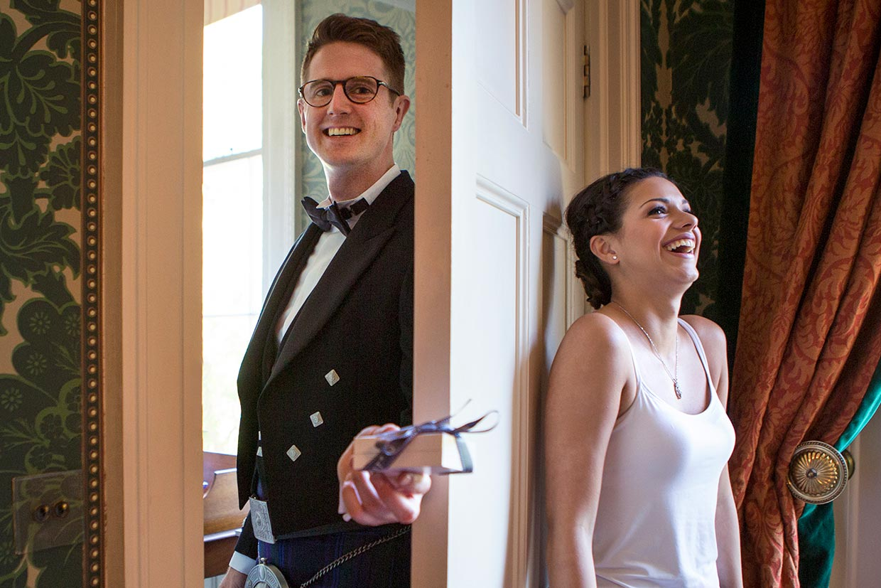 A wedding photograph of a relaxed fun bride and groom. The groom is passing a gift to the bride, the bride is hiding behind the door.